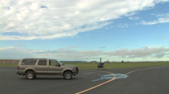 Helicopter next to SUV taking off and flying off in distance Stock Footage