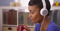 African woman jamming to music with mug Stock Footage