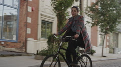 Low angle medium tracking shot of young woman riding bicycle on urban street / Stock Footage
