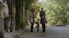 Wide shot of young women walking with bicycle on cobblestone street / New York Stock Footage