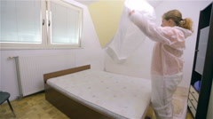 Woman roll out plastic foil to cover furniture Stock Footage
