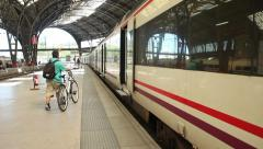 Man on a bike boards train in old style train station Stock Footage