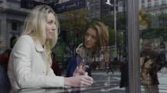 Medium shot of young women using digital tablet at urban cafe window / New York Stock Footage