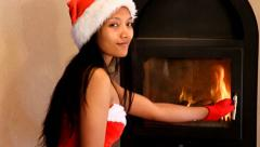 Girl in costume of Santa Claus gives the wood in the stove Stock Footage