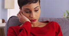 Sad African woman sitting on couch - stock footage