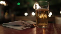 Pint glass of lager and newspaper on pub table - stock footage