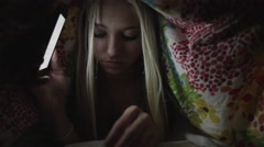 Close up of teenage girl reading book with cell phone flashlight under blanket Stock Footage