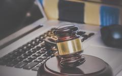 Law legal concept photo of gavel on computer with legal books in background. Stock Photos
