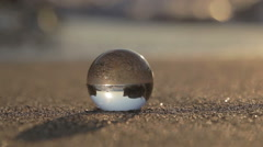 Glass sphere on a sandy beach Stock Footage
