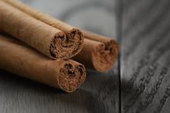 true cinnamon sticks on wooden table - stock photo