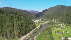 Flight with decrease over river and  village in mountains. Aerial shot Stock Footage