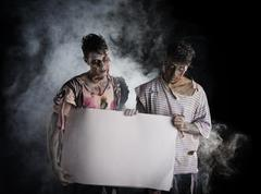 Two male zombies holding empty white banner Kuvituskuvat