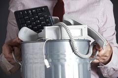 Businessman holding garbage can with obsolete office equipment Stock Photos