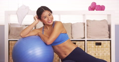 Cute Japanese woman resting on exercise ball Stock Footage