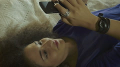 Beautiful curly woman lying on the bed is using smartphone: mobile phone Stock Footage