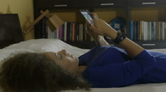 Young woman lying down in bed at home texting and playing on mobile phone Stock Footage