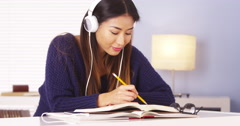 Japanese woman listening to music while doing homework Stock Footage