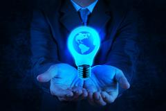 Businessman hand shows light bulb with planet earth Stock Illustration