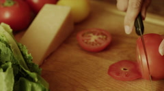 Close up high angle panning shot of woman slicing tomato on cutting board / Stock Footage