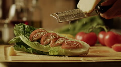 Slow motion close up panning shot of cheese being grated over lettuce and tomato - stock footage