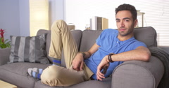 Attractive Mexican man lying on couch Stock Footage