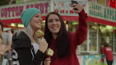 Medium shot of young women eating taffy apples and taking self-portraits with Stock Footage