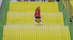 Medium shot of mother and daughter on large slide at amusement park / Salt Lake Stock Footage