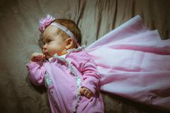 Image of cute little girl in pink suit and cloak indoor Stock Photos