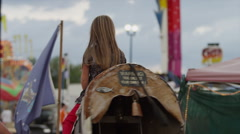 Slow motion medium shot of girl riding mechanical bull at amusement park / Salt Stock Footage