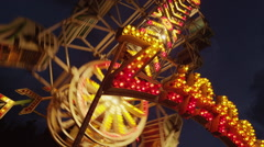 Low angle panning medium shot of spinning zipper ride against night sky at Stock Footage