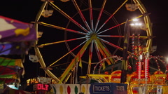 Slow motion wide shot of Ferris Wheel at amusement park at night / Salt Lake Stock Footage