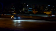Heavy freeway traffic at night with downtown San Diego in background Stock Footage