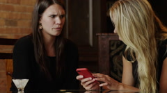 Close up shot of young women talking and using cell phone at cafe / American Stock Footage