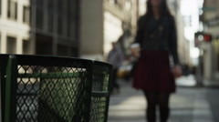 Close up slow motion of woman throwing coffee cup in city garbage can / New York Stock Footage