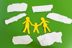 Paper cutout family with expenses on torn paper scraps Stock Photos