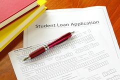 student loan application with books and pen - stock photo