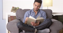 Puerto Rican man reading a book at home Stock Footage
