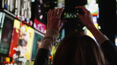 Close up panning shot of young woman using camera phone in Times Square at night Stock Footage