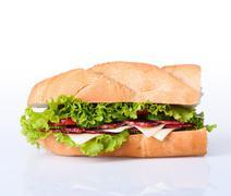 sandwiches - turkey breast, ham & swiss and salami on a cutting board. - stock photo