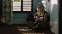 Slow motion medium shot of teenage girl writing music and playing guitar / Stock Footage