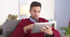 Mexican guy using his tablet on couch Stock Footage