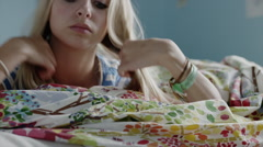 Close up of serious teenage girl laying on bed / Sandy, Utah, United States Stock Footage