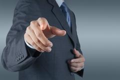 Businessman pressing an imaginary button on virtual screen Stock Photos