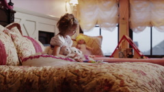 Medium shot of girl reading book to stuffed animals on bed / Sandy, Utah, United Stock Footage