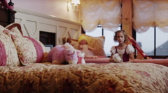Medium shot of girl playing with stuffed animals on bed / Sandy, Utah, United Stock Footage