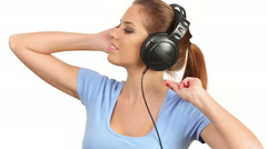 Beautiful lady listening music on large headphones, looking at camera Stock Footage