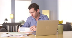 Man handling personal finances at desk - stock footage