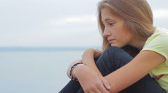 Sad Upset Teen Girl Sitting On Beach In Evening HD Stock Footage