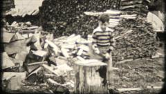 1202 - young boy is chopping firewood out back - vintage film home movie Stock Footage