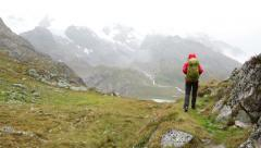 Hiking - hiker woman on trek with backpack in rain on mountain in Swiss alps Stock Footage